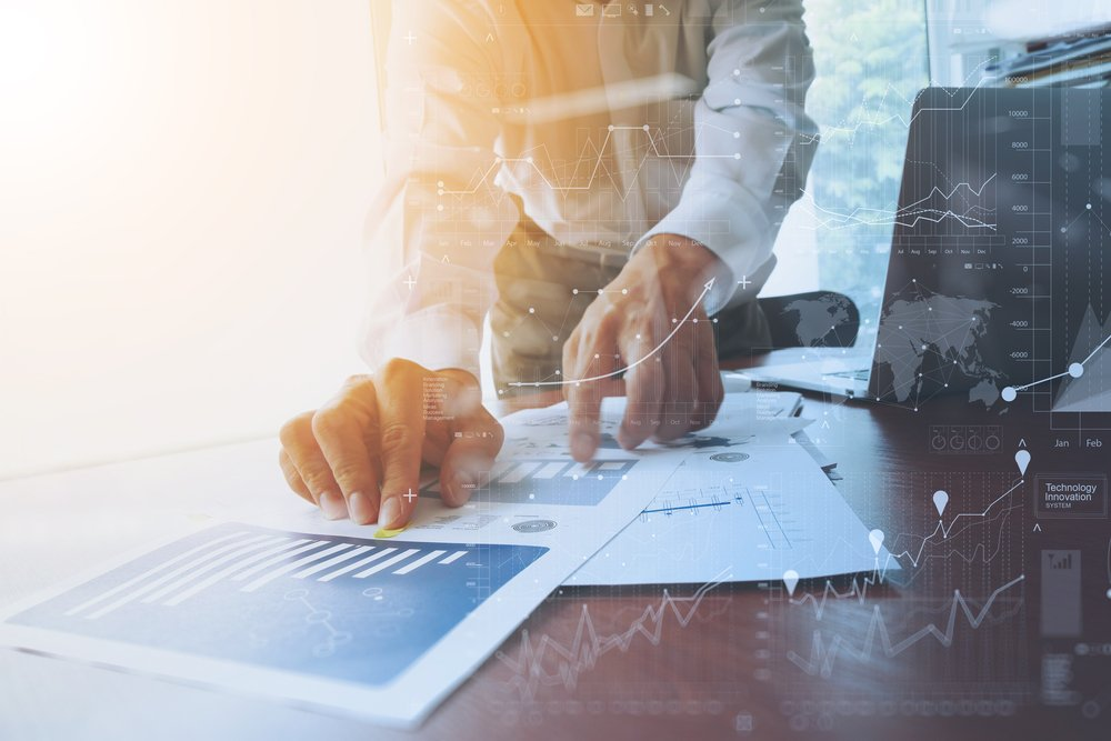 business documents on office table with smart phone and digital tablet and graph financial with social network diagram and man working in the background